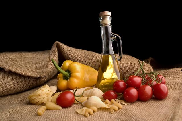 na jutě je sklenice s olejem, rajčata, poházené těstoviny, paprika