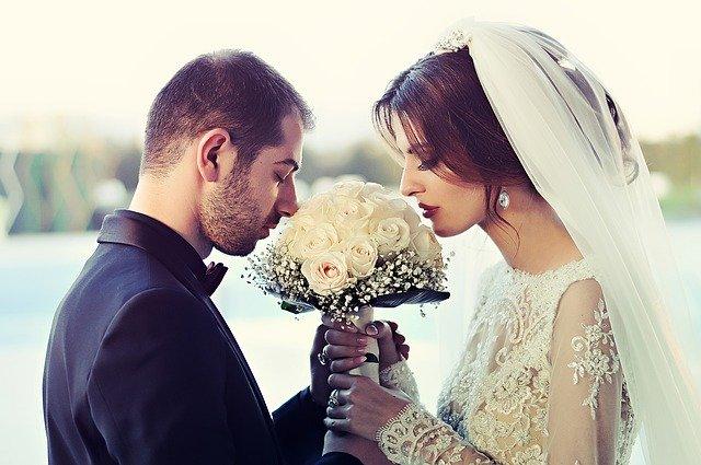 nevěsta se ženichem čichající ke svatební kytici
